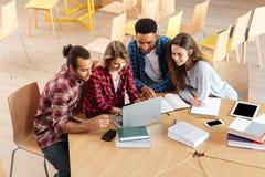 Studenti concentrati che si siedono nella biblioteca facendo uso del computer portatile Fotografia Stock Libera da Diritti