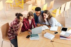 Studenti concentrati che si siedono nella biblioteca facendo uso del computer portatile Fotografie Stock Libere da Diritti
