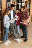 Studenti concentrati che stanno in libro di lettura delle biblioteche Immagini Stock