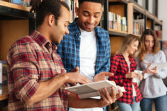 Studenti concentrati degli uomini che stanno in libro di lettura delle biblioteche Fotografia Stock Libera da Diritti