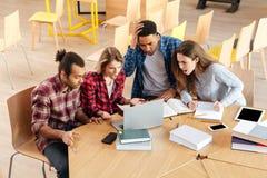 Studenti confusi tristi che si siedono nella biblioteca facendo uso del computer portatile Fotografia Stock Libera da Diritti
