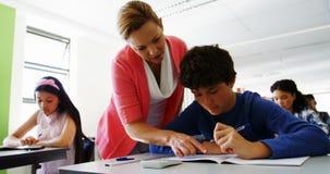 Studenti d'aiuto dell'insegnante con il loro compito in classe stock footage