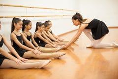 Studenti d'aiuto dell'insegnante di ballo con posizione Immagini Stock