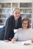 Studenti d'aiuto dell'insegnante femminile su classe Fotografia Stock Libera da Diritti