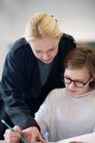 Studenti d'aiuto dell'insegnante femminile su classe Immagine Stock