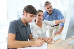 Studenti d'aiuto di professore nella classe Immagine Stock