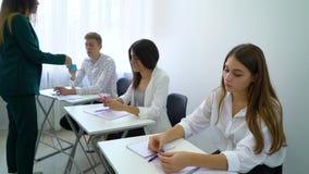 Studenti d'istruzione del giovane insegnante e dare la carta di compito in aula archivi video