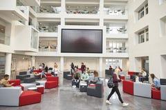 Studenti davanti allo schermo in atrio dell'università moderna Fotografia Stock Libera da Diritti