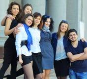 Studenti degli amici che stanno davanti all'istituto Immagine Stock