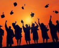 Studenti del gruppo che celebrano concetto della siluetta di graduazione Fotografia Stock