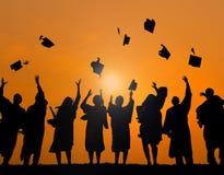 Studenti del gruppo che celebrano concetto della siluetta di graduazione Fotografia Stock Libera da Diritti