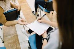 Studenti del primo piano che scrivono e che parlano su un fondo dell'aula Nuovo concetto del materiale di studio Immagine Stock