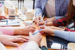 Studenti del primo piano che scrivono su un fondo della tavola La gente che lavora con le carte ed i dispositivi Concetto di prog Fotografia Stock Libera da Diritti