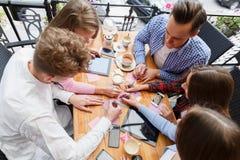 Studenti del primo piano che scrivono su un fondo della tavola La gente che lavora con le carte ed i dispositivi Concetto di prog Fotografia Stock