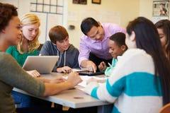 Studenti della High School con i computer portatili di In Class Using dell'insegnante Immagine Stock