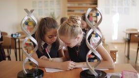 Studenti della High School nello studio dell'uniforme scolastico la struttura di DNA in una classe di Biologia archivi video