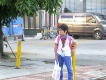 Studenti della scuola primaria che aspettano lo scuolabus Fotografia Stock