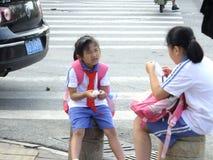 Studenti della scuola primaria che aspettano lo scuolabus Immagine Stock