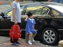 Studenti della scuola primaria che aspettano lo scuolabus Fotografie Stock