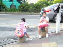 Studenti della scuola primaria che aspettano lo scuolabus Immagini Stock