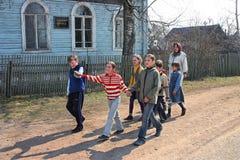 Studenti della scuola primaria rurale, camminanti in via del villaggio, Rus Immagine Stock