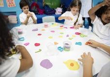 Studenti di asilo che imparano forma con argilla variopinta Immagini Stock