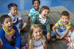 Studenti di asilo che si siedono sul pavimento Fotografia Stock