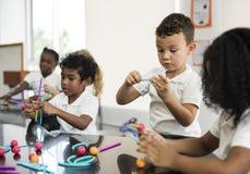 Studenti di asilo che tengono apprendimento delle strutture dai giocattoli Fotografia Stock