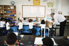 Studenti di asilo che tengono apprendimento delle strutture dalla t Fotografia Stock