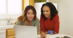 Studenti di college afroamericani ed asiatici che per mezzo del computer portatile per studiare Immagini Stock Libere da Diritti