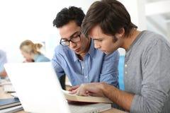 Studenti di college in aula con i libri ed il computer portatile Fotografia Stock