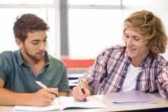 Studenti di college che si siedono nell'aula Immagine Stock Libera da Diritti