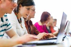 Studenti di college che si siedono in un'aula Immagini Stock Libere da Diritti