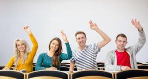Studenti di college che sollevano le mani nell'aula immagine stock libera da diritti