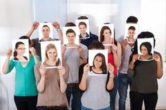 Studenti di college che tengono le fotografie davanti ai fronti immagine stock libera da diritti