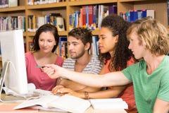 Studenti di college che utilizzano calcolatore nella libreria Immagini Stock Libere da Diritti