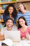 Studenti di college che utilizzano computer portatile nella biblioteca immagini stock libere da diritti