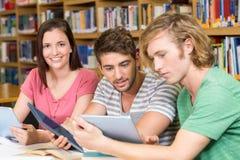 Studenti di college che utilizzano le compresse digitali nella biblioteca fotografie stock
