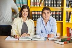 Studenti di college con i libri che si siedono alla Tabella dentro Immagine Stock