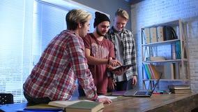 Studenti di college felici che per mezzo del computer della compressa archivi video