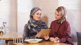 Studenti di college musulmani femminili che utilizzano il computer della compressa nel caffè video d archivio