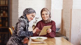 Studenti di college musulmani femminili che utilizzano il computer della compressa nel caffè archivi video