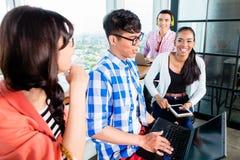 Studenti di college nell'apprendimento di gruppo di lavoro Immagine Stock