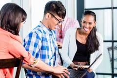 Studenti di college nell'apprendimento di gruppo di lavoro Immagine Stock Libera da Diritti