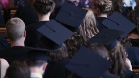 Studenti di economia di laurea che guardano cerimonia di assegnazione del diploma di istruzione superiore archivi video