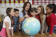 Studenti di Explaining Globe To dell'insegnante Fotografie Stock Libere da Diritti