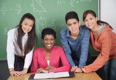 Studenti di With High School dell'insegnante allo scrittorio Immagini Stock Libere da Diritti