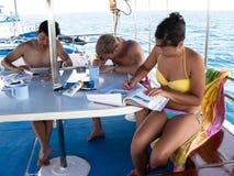Studenti di immersione con bombole che studiano la barca a bordo di tuffo Fotografia Stock Libera da Diritti