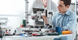 Studenti di ingegneria che per mezzo di una stampante 3D fotografie stock libere da diritti