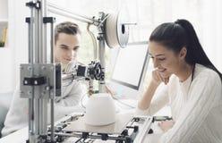 Studenti di ingegneria che utilizzano una stampante 3D nel laboratorio fotografia stock libera da diritti